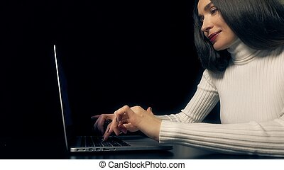Beautiful brunette woman working on her laptop against black background