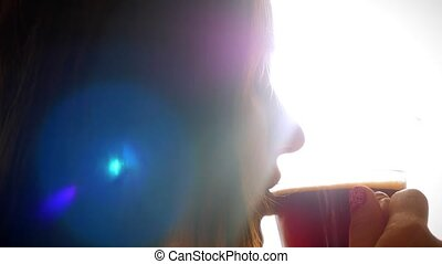 Beautiful brunette young woman drinks coffee in cafe at sunlight