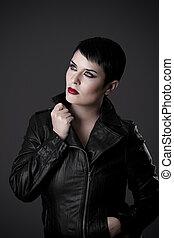 beautiful brunette young woman in black leather jacket, studio shot