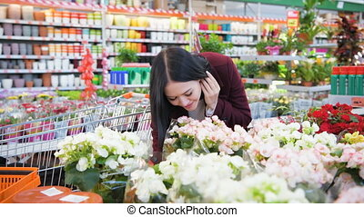 Beautiful brunette young woman smelling flowers in garden shop supermarket place female gardener hands gently touching spring flower shopping mall store green house store bloom plants
