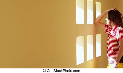 beautiful brunette young woman standing near white wall with small windows