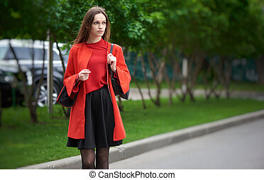 Beautiful brunette young woman wearing red jacket and walking on the street