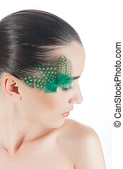 Beautiful brunette young woman with peacock style make-up