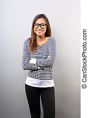 Beautiful business latina woman in glasses smiling with folded arms on empty copy space background.