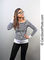 Beautiful business latina woman in glasses smiling with hand near the face and looking up on empty copy space background.