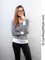 Beautiful business laughing latina woman thinking in glasses with hand under the face on empty copy space background.