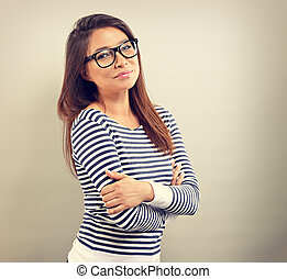 Beautiful business positive woman in glasses looking with thinking look on empty space background. Vintage portrait