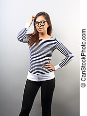 Beautiful business serious woman in glasses looking and scratched the head with thinking look on empty space background.