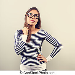 Beautiful business serious woman in glasses looking up and scratched the head with thinking look on empty space background. Toned closeup portrait