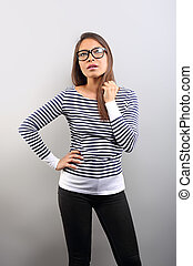 Beautiful business serious woman in glasses looking up and scratched the head with thinking look on empty space background.