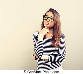 Beautiful business serious woman in glasses looking with hand under the face with thinking look on empty space background. Toned vintage portrait