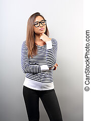 Beautiful business serious woman in glasses looking with hand under the face with thinking look on empty space background.