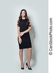Beautiful business woman in black dress standing against white wall background