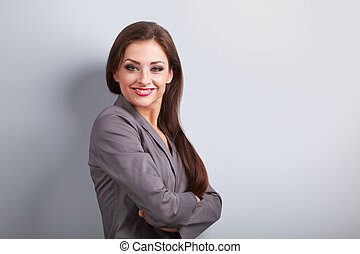Beautiful business woman in suit smiling on blue background with empty copy space