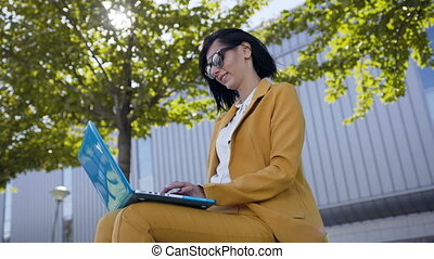 Beautiful business woman in sunglasses dressed in suit using laptop computer during break outdoors, Young woman sitting on the bench in the park near business centre office