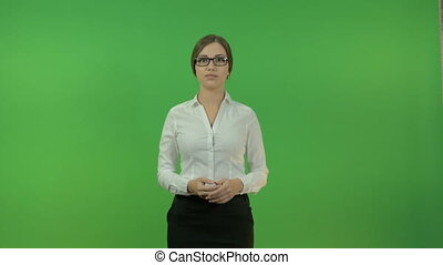 Beautiful business woman making a presentation. On the background of a green screen. She is dressed in a white blouse and black skirt.