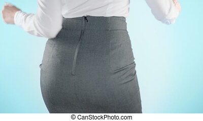 Beautiful business woman on a colored background. close-up skirt. dress code, move the hips. 4k, slow motion