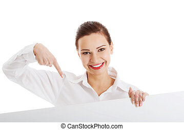 Beautiful business woman pointing on copy space.