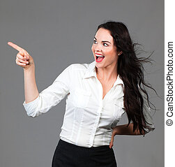 Beautiful business woman pointing to copyspace