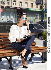 Beautiful business woman sitting on a bench