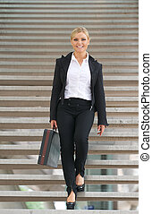 Beautiful business woman walking downstairs with briefcase