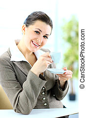 Beautiful business woman with a cup looking at camera