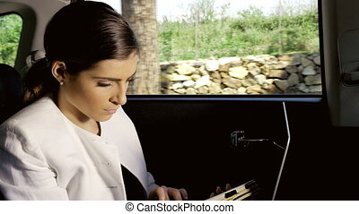 Beautiful business woman working in back of car with tablet closeup