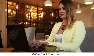 Beautiful business woman working using a mobile computer in a cafe.