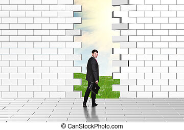Beautiful businessman watching dilapidated brick wall