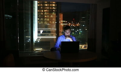 Beautiful businessman working overtime at night in executive...