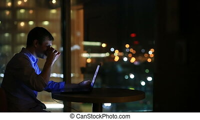 Beautiful businessman working overtime at night in executive office. City lights are visible in background from a large window