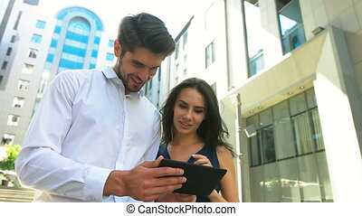 Beautiful businesswoman and her handsome colleague using tablet in the street.