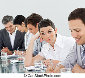 Beautiful businesswoman bored at a presentation with her team