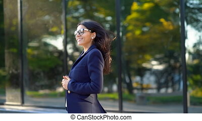 Beautiful businesswoman coming out from office building in...