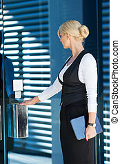 Beautiful businesswoman entering the office with tablet for a meeting.