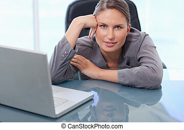 Beautiful businesswoman leaning on her desk
