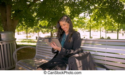 Beautiful businesswoman on her digital tablet touchpad dolly...
