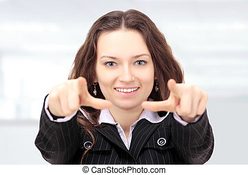 Beautiful businesswoman shows a forward index fingers in the office.