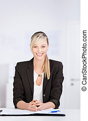 Beautiful businesswoman sitting at her office desk