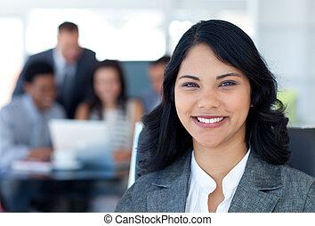 Beautiful businesswoman smiling with her team working in office