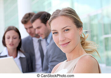Beautiful businesswoman standing outside in front of team