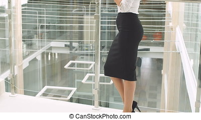 Beautiful businesswoman stands with tablet computer in office building.