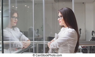 Beautiful businesswoman stands with tablet computer in office building. Slow motion