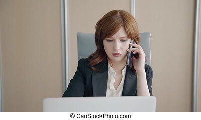 Beautiful businesswoman talking on phone sitting front of laptop screen in company.