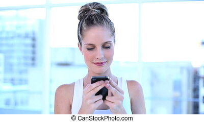 Beautiful businesswoman texting with her mobile phone in a...