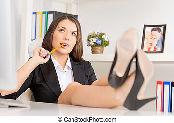 beautiful businesswoman thinking with feet on table. attractive brunette sitting in office and working