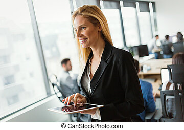 Beautiful businesswoman using digital tablet in office