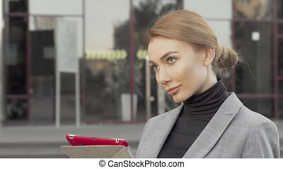 Beautiful businesswoman using digital tablet outdoors in the city
