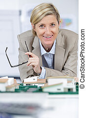 beautiful businesswoman with house model made from scale