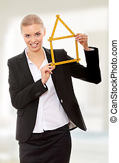 Beautiful businesswoman with house model